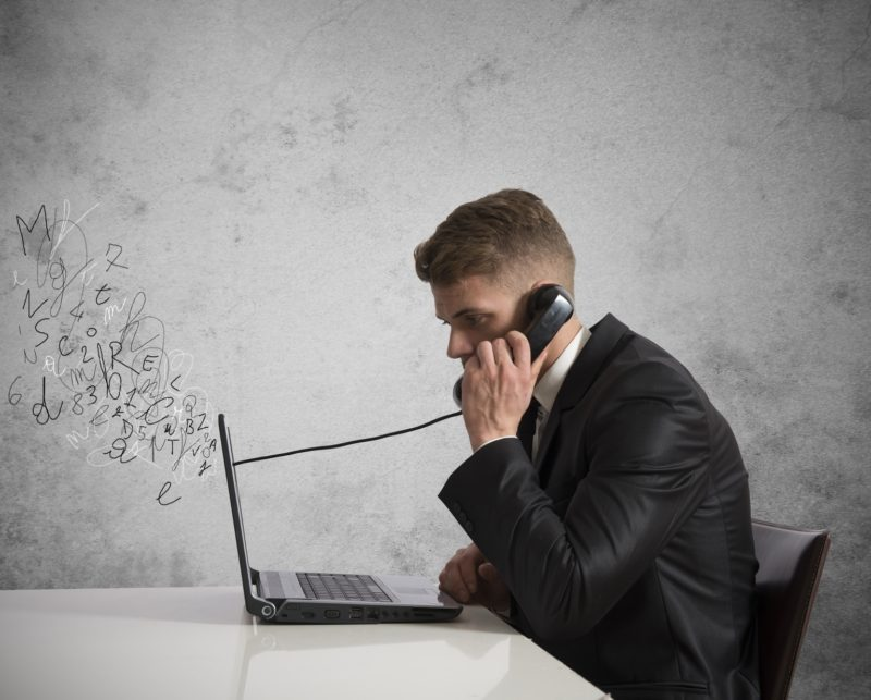 Man using phone connected to computer indicating VoIP calling