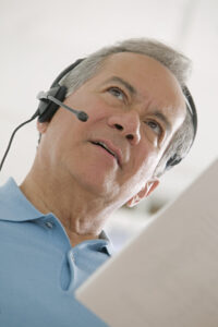 Man Using a Telephone Headset looking at his phone bill.