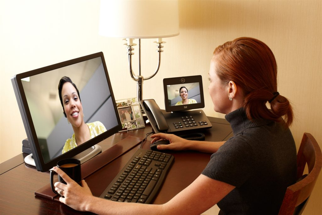 Two business women video conferencing remotely